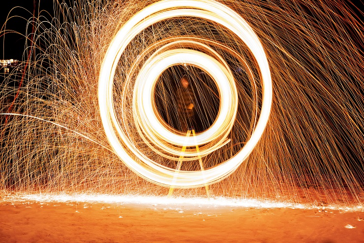Sparks photographed with slow shutter to form circle. Smaller circle within larger. Warm orange colors contrasted on dark background.